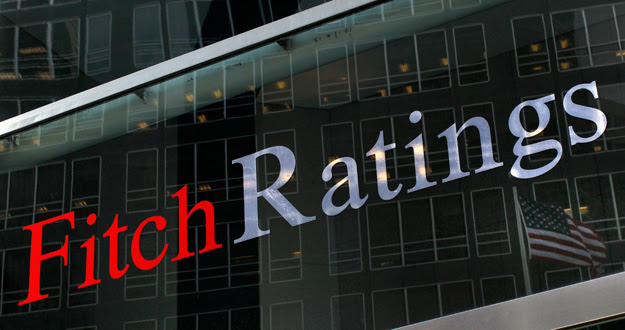 A flag is reflected on the window of the Fitch Ratings headquarters in New York