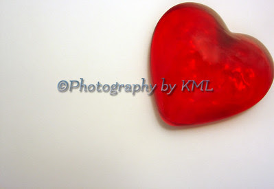 a red glass paperweight in the shape of a heart