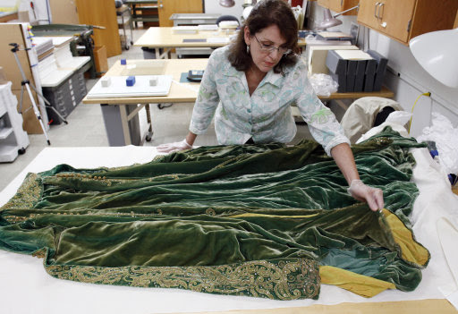 "Cara Varnell, an independent art conservator who specializes in Hollywood film costumes, works with the green velvet gown from the film ""Gone With the Wind,"" Tuesday, July 19, 2011, in Austin, Texas. The Harry Ransom Center at the University of Texas is working to preserve five of the dresses acquired with the collection of film producer David O. Selznick in the 1980s.  (AP Photo/Eric Gay)"