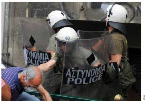 A Greek protester clashes with riot police in Athens in June 2011.