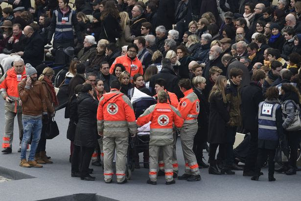 "Members of the French Red Cross accompany people wounded in the Paris terror attacks, as they arrive for the ""national and republican"" tribute, a solemn ceremony in honour of the 130 people killed in the November 13 Paris attacks"