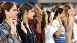 A growing percentage of new Canadians, like these seen reaffirming their vows of citizenship before a Toronto Blue Jays game in 2003, will be visible minorities, according to a new report by Statistics Canada.