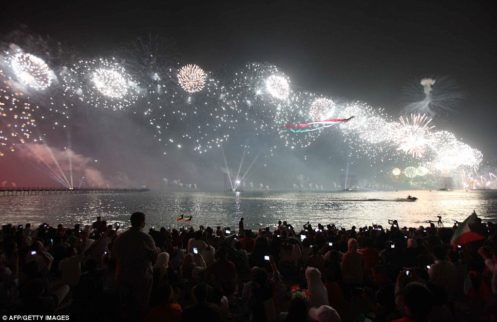 Revelers wave Kuwaiti flags in the foreground as the fireworks burst above the Persian Gulf