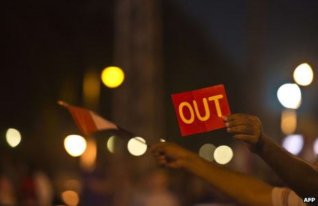 "A man holds up a ""red card"" outside the presidential palace in Cairo, late on 29 June"