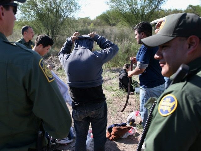 Undocumented immigrants remove items of clothing while being searched by U.S. Border Patrol agents who caught them on December 7, 2015 near Rio Grande City, Texas.
