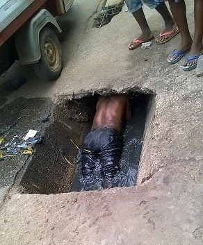 Man Who Allegedly Drinks 'Ogogoro' Like Water Spotted Swimming Inside a Dirty Gutter (See Photos)