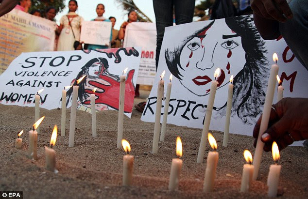 Vigil: Candles were lit in Delhi as silent protestors stood displaying placards, banners and posters