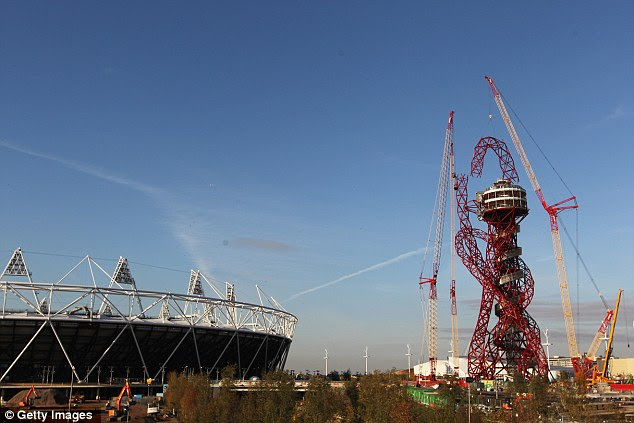 Monument: Builders lower the final piece of the ArcelorMittal Orbit sculpture into place at the Olympic Park yesterday