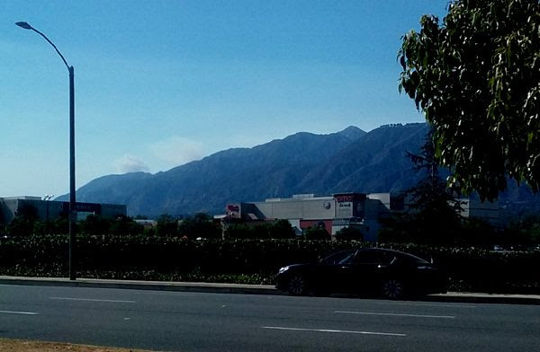 A cloud of smoke is visible (towards the left of this image) behind the San Gabriel Mountains near Santa Anita Mall...on July 24, 2016.