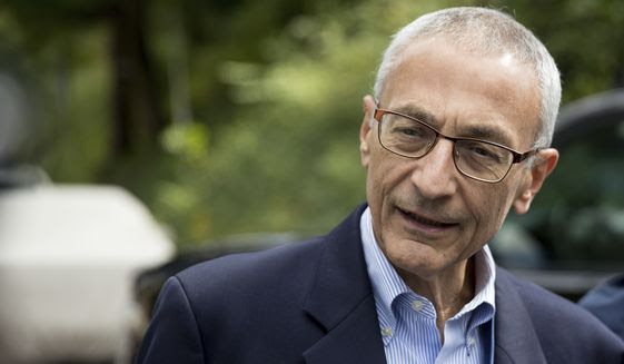 In this photo taken Oct. 5, 2016 file photo, Hillary Clinton's campaign manager John Podesta speaks to members of the media outside Democratic presidential candidate Hillary Clinton's home in Washington. Hacked emails reveal internal disagreement among top Clinton aides about her determination to hold a Clinton Foundation summit in Morocco that later drew attention over its reliance on large donations from foreign governments.  (AP Photo/Andrew Harnik, File)