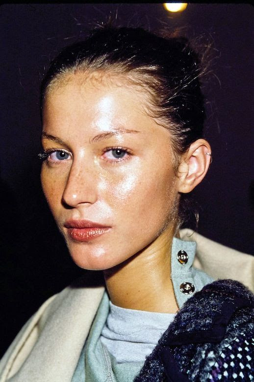 Le Fashion Blog Beauty Glowing Skin Gisele Bundchen Bun White Coat Blue Sweater Tee Via Vogue