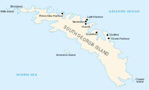 """Outline of a long, narrow irregular-shaped island with small islands around its coasts. The main island is labelled """"South Georgia"""", and various place names are shown on its north coast including Stromness Husvik and Grytviken."""