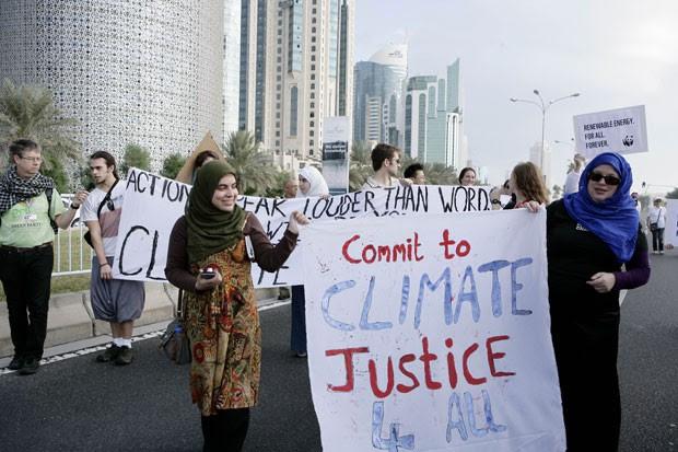 Mulheres seguram cartazes pedindo justiça climática para todos os países (Foto: Osama Faisal/AP)