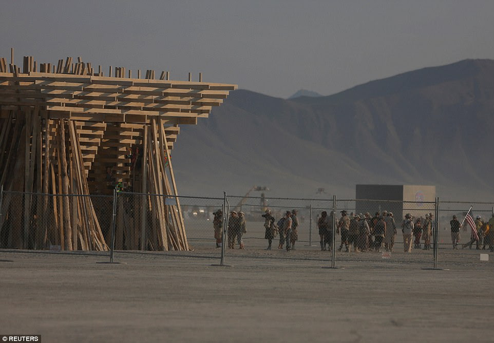 A chainlink fence surrounds The Temple before its burn - hundreds of festival goers unwind nearby ahead of the fire later in the night