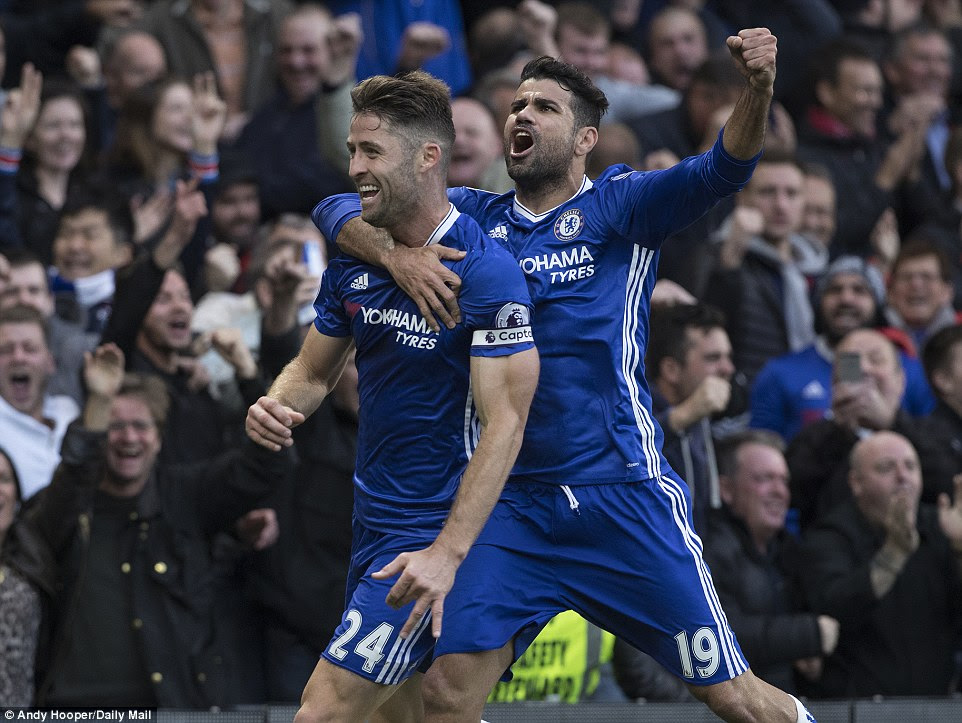 Cahill (left) is congratulated by team-mate Diego Costa as Chelsea fans celebrate a two-goal lead against United