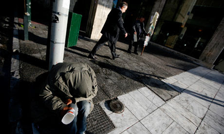 A homeless man begs for money in Athens