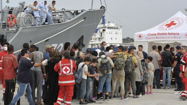 Migrants enter Red Cross tent after disembarking from Croatian Coast Guard ship at Augusta harbour, near Siracusa, Sicily, Italy. 16, Aug 2015.