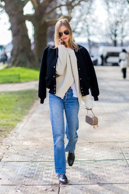Le Fashion Blog Street Style Pfw Black Varsity Style Bomber Jacket Ribbed Cream Cardigan White Tee Mini Bag Raw Hem Vintage Jeans Boots Via Harpers Bazaar Australia