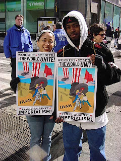 """Photo: placard with cartoon of people in Iran spiking the American boot with a red flag; text: """"Workers, soldiers, the world, unite! Fight against imperialism!"""""""
