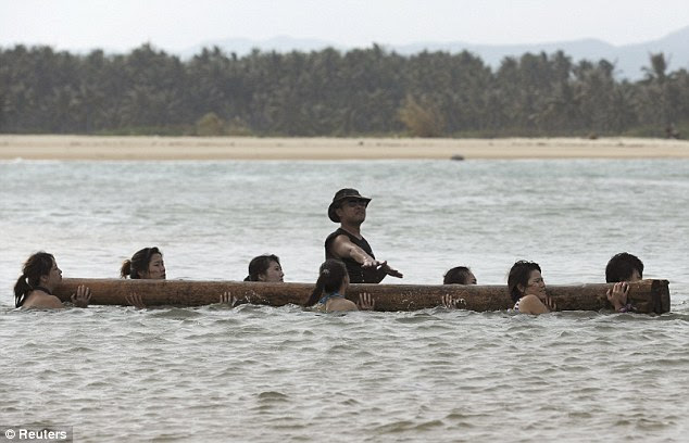 In demand: The trainees carry a heavy log on their shoulders as they walk through the sea