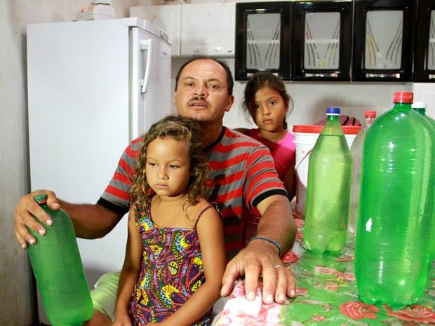 O pescador Jorge Souza mostra garrafas de água doce que armazena para o consumo da família (Foto: Waldson Costa/G1)
