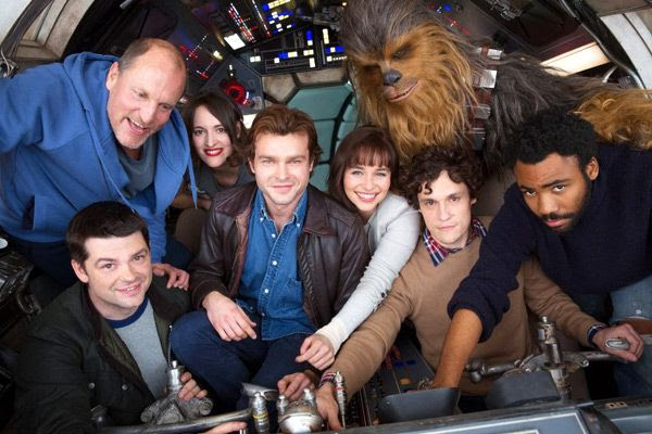The main cast of the untitled Han Solo spin-off film pose inside the cockpit of the Millennium Falcon.