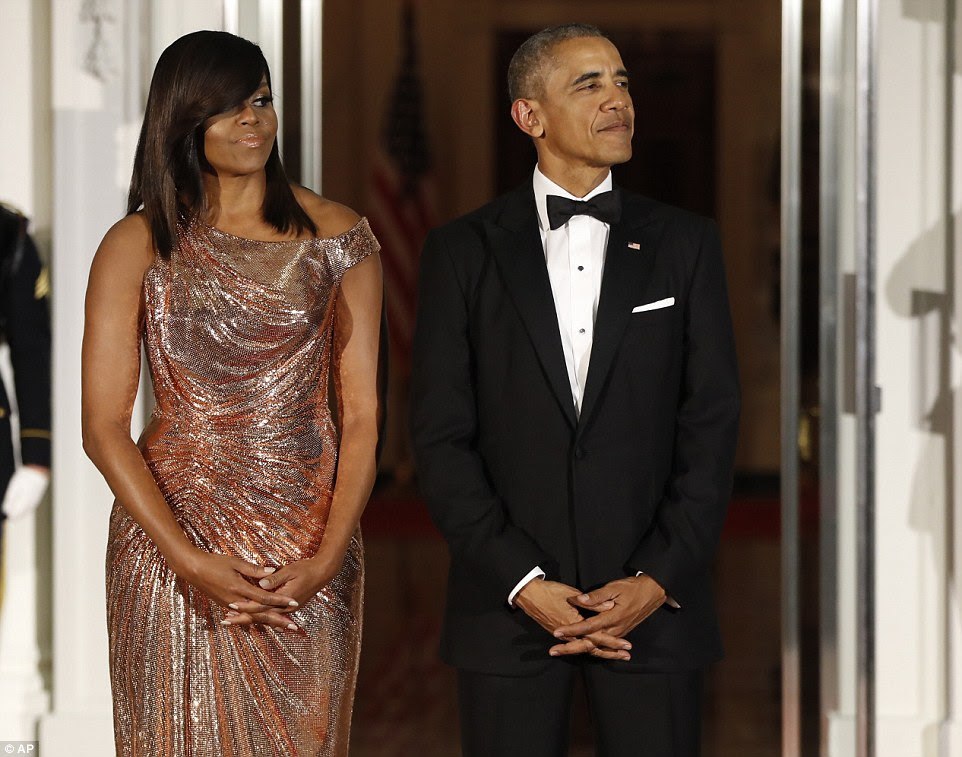 President Barack Obama and first lady Michelle Obama wait to greet Italian Prime Minister Matteo Renzi and his wife Agnese Landini on the North Portico for a State Dinner at the White House in Washington last night