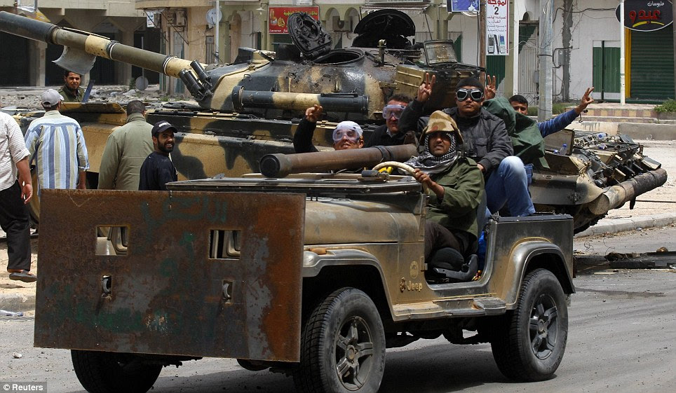 Victory: Rebel fighters were today celebrating pushing loyalists out of Tripoli STreet in their makeshift armoured Jeep as they drive past a captured Gaddafi tank