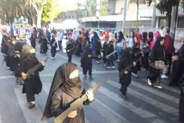 Children wearing a burqa and holding cut-out weapons in parade