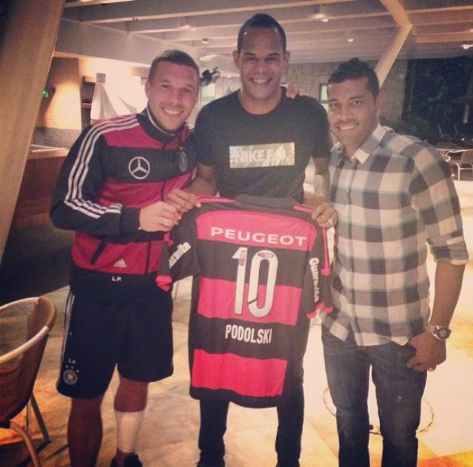Podolski com André Santos mostra camisa do Flamengo