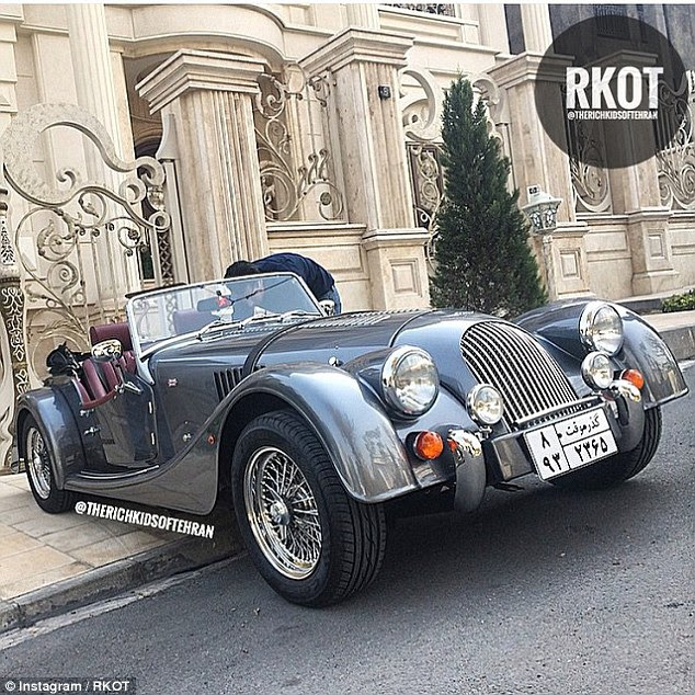 Talvez o carro mais impressionante é um conversível estilo vintage estacionado do lado de fora de uma casa palaciana
