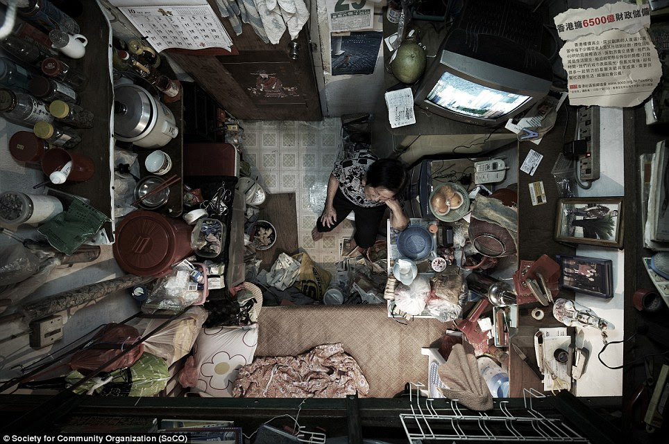 Pile it high: A woman sits in the only available space in her room. Campaign groups say many Hong Kong residents are being neglected by the city's decision-makers