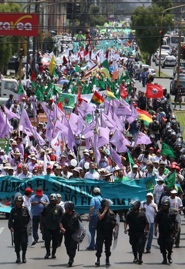"""Thousands march in """"Defense of Mother Earth"""" in Lima, Peru, Wednesday, Dec. 10, 2014. Thousands marched in support of Mother Earth as they chanted slogans ag..."""