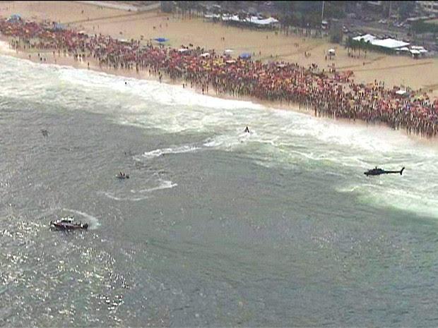 Equipes de socorro do Corpo de Bombeiros fazem as buscas ao helicóptero na Praia de Copacabana, neste sábado (29) (Foto: Reprodução/TV Globo)