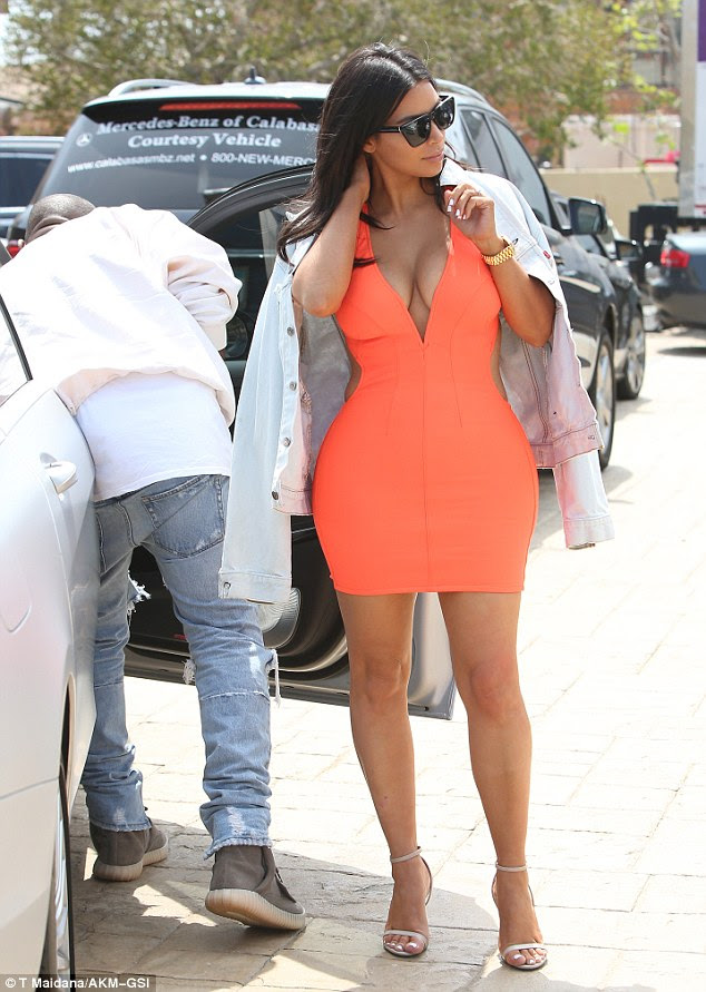 Body con: Kim Kardashian showed off her curves in a skintight orange dress while on a lunch date with husband Kanye West in Malibu on Saturday