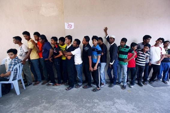 Rohingya men stand in a line at a centre to register for a temporary card issued by the United Nations High Commissioner for Refugees (UNHCR) in Kuala Lumpur in this February 27, 2014 file photo.  REUTERS-Samsul Said