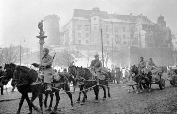 Radzieccy żołnierze z jednostki artyleryjskiej - konie ciągną niewidoczne na tym kadrze działa, a w tle widać zamek królewski na Wawelu. Tuż po wycofaniu się wojsk niemieckich, ale jeszcze przed całkowitym zajęciem Krakowa przez Armię Czerwoną, Polacy utworzyli straż na Wawelu, by chronić zamek i katedrę przed szabrownikami.