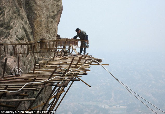 Not so high spec: Workers built a 3ft-wide plank road on the side of Shifou Mountain, in Hunan Province, China earlier this year