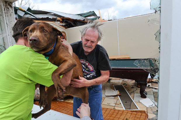 O americano passa sua cachorra pela janela para um vizinho após encontrá-la na casa destruída (Foto: AP/Gary Cosby Jr./The Decatur Daily)