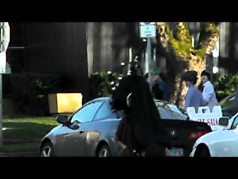 video que muestra a un hombre disfrazado de Darth Vader, tocando una gaita, y conduciendo un monociclo