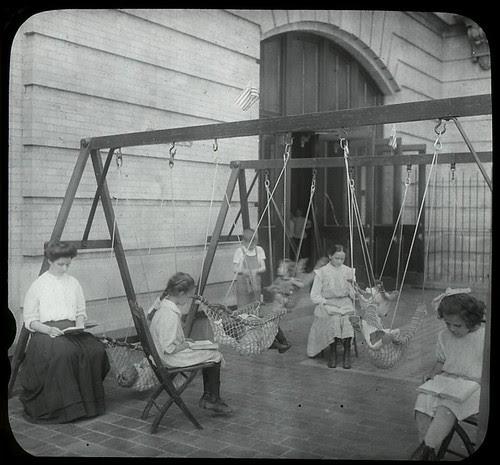 Women and girls reading near swingset where younger children... por New York Public Library
