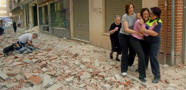 Pessoas passam em meio a destroços em rua de Lorca, na Espanha, após terremoto