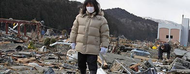 A woman searches for her missing husband through the earthquake and tsunami-hit town of Minamisanriku, Miyagi Prefecture, Friday, March 18, 2011. (AP)