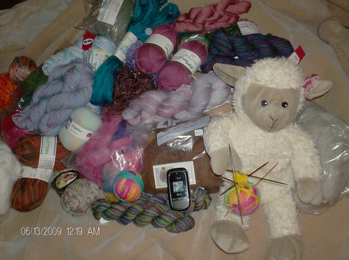 Joy's yarn stash with Sheepy the toy sheep and my knitted sock in front of my yarn stash