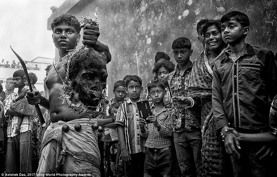In a remote village of India's West Bengal, children gather as this Sannyasi (religious beggar) parades a skull as part of a Gajan Festival, in hopes for rain and a better harvest in the coming year