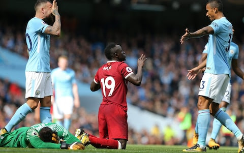 Sadio Mane protests his innocence as Ederson clutches his face