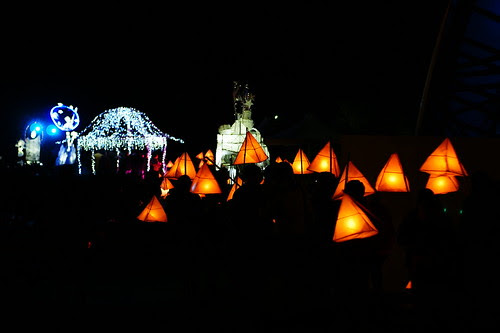 the yellow pyramid lanterns and silhouetted carriers gather around a gazebo covered in white fairy lights, while the larger sculpture-lanterns continue past