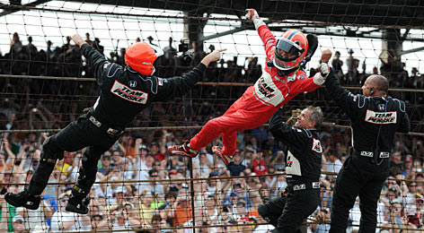 """Helio Castroneves does his trademark """"Spiderman"""" victory celebration by climbing the frontstretch fence with members of his crew."""