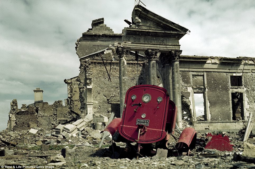 Ruins: A bombed-out Palais de Justice is shown in front of a heavily damaged fire engine in the town of St Lo, France, shortly after the D-Day offensive
