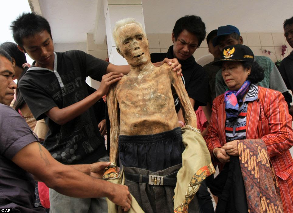 The ritual is held once every few years when family members gather to clean the graves and change the clothes of their deceased relatives to honor their spirits